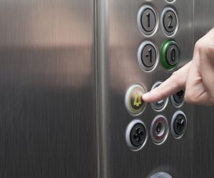 Man pressing the alarm button in the elevator with his forefinger